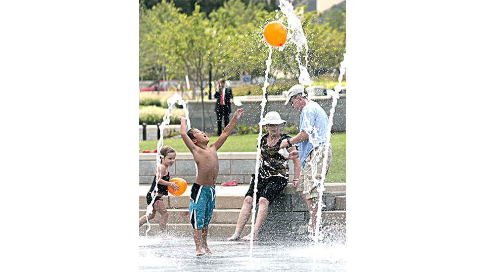pack square park asheville - boy playing with a balloon at a splash park