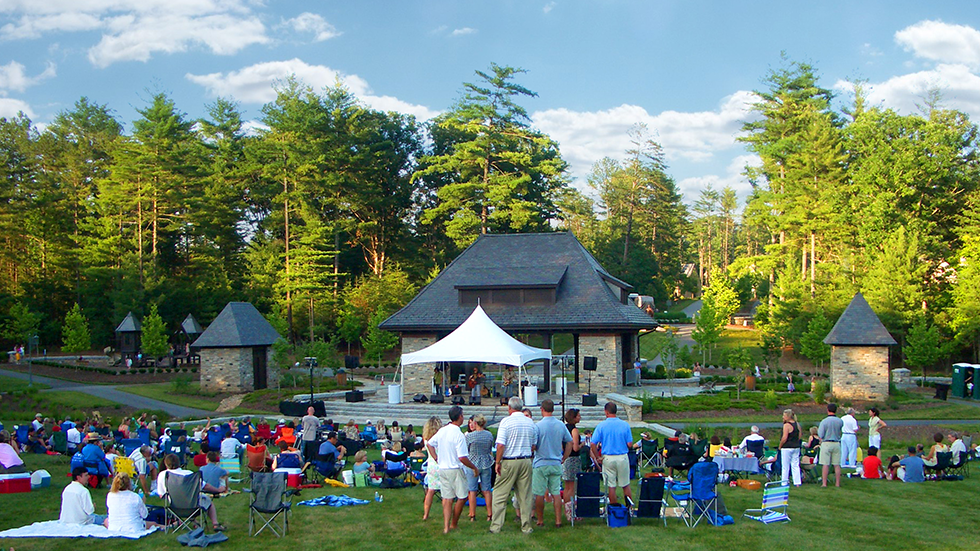 view of an outdoor concert at a stone pavillion with people watching from the lawn