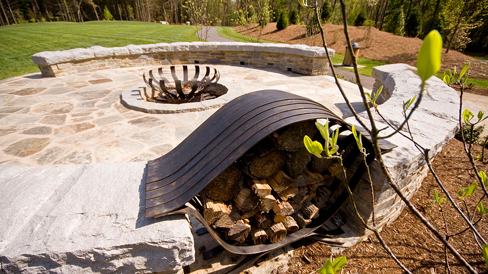 custom art firepit and wood holder at natural stone patio
