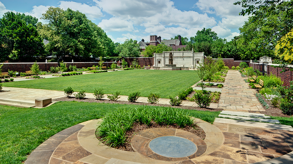 open event lawn surrounded by garden plantings and brick wall historic fountain