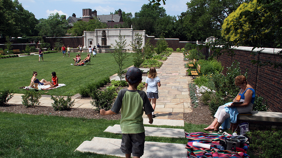 kids playing people sunbathing and strolling through walled garden on a sunny day