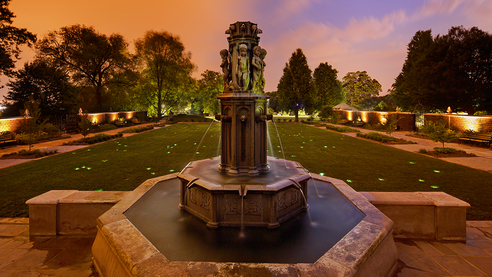 historic fountain in walled garden with lights at dusk