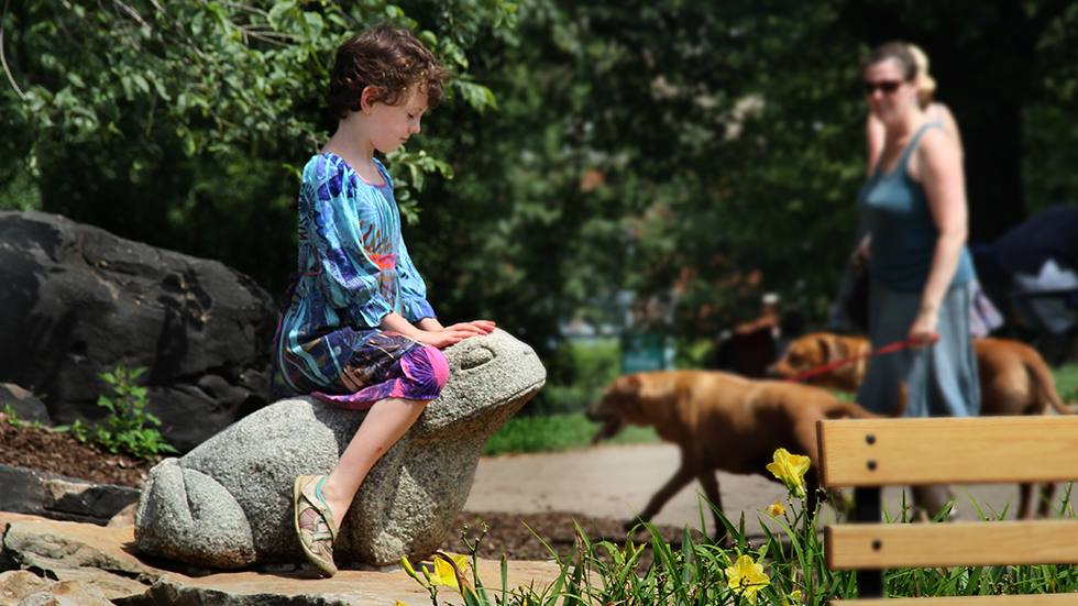 girl sitting on stone frog sculpture